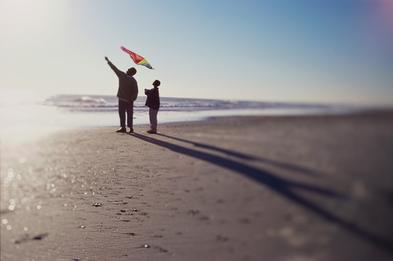 Silhouette of a father and son flying a kite on th