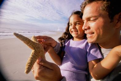 Close-up of a man showing his daughter a starfish